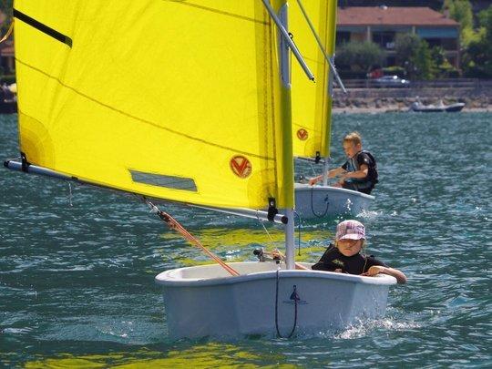 Zwei optimisten folgen dem Segellehrer