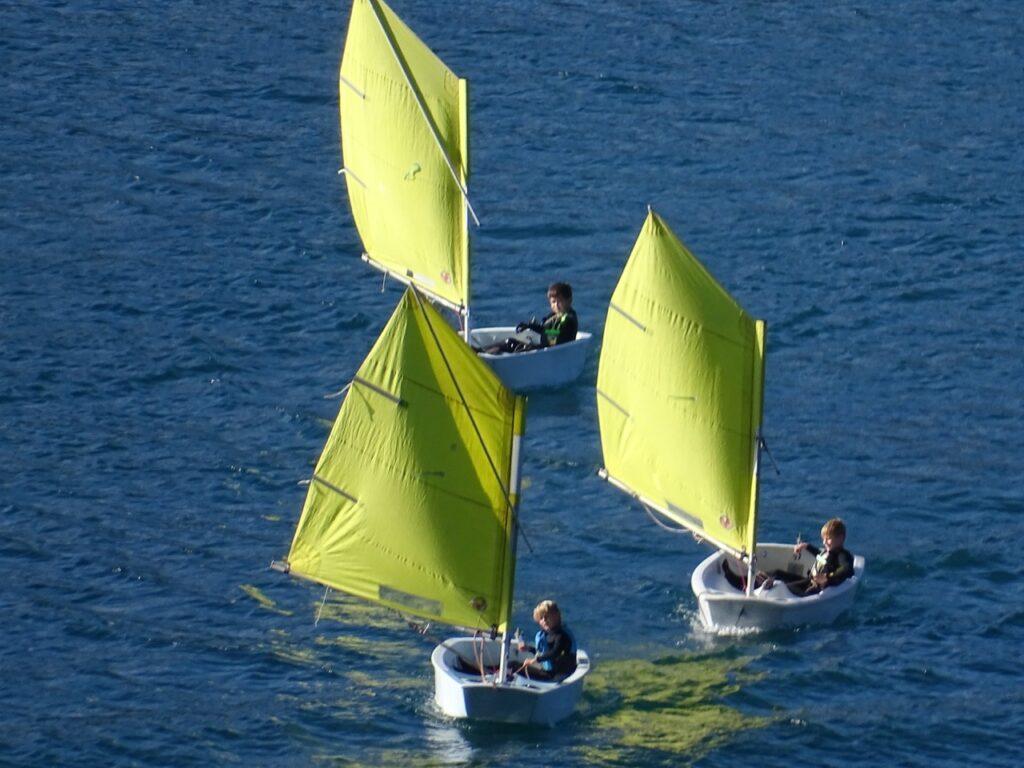 drei Kindersegelboote mit gelben Segeln