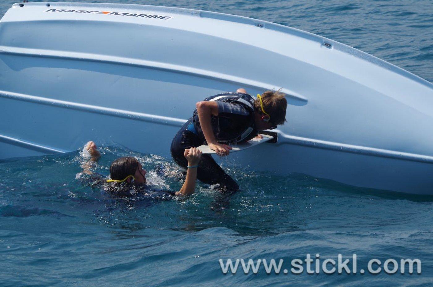 gekentertes Segelboot mit zwei jungen Seglern