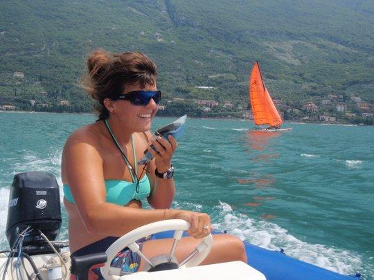 Segel-Trainerin mit Funkgerät im Motorboot