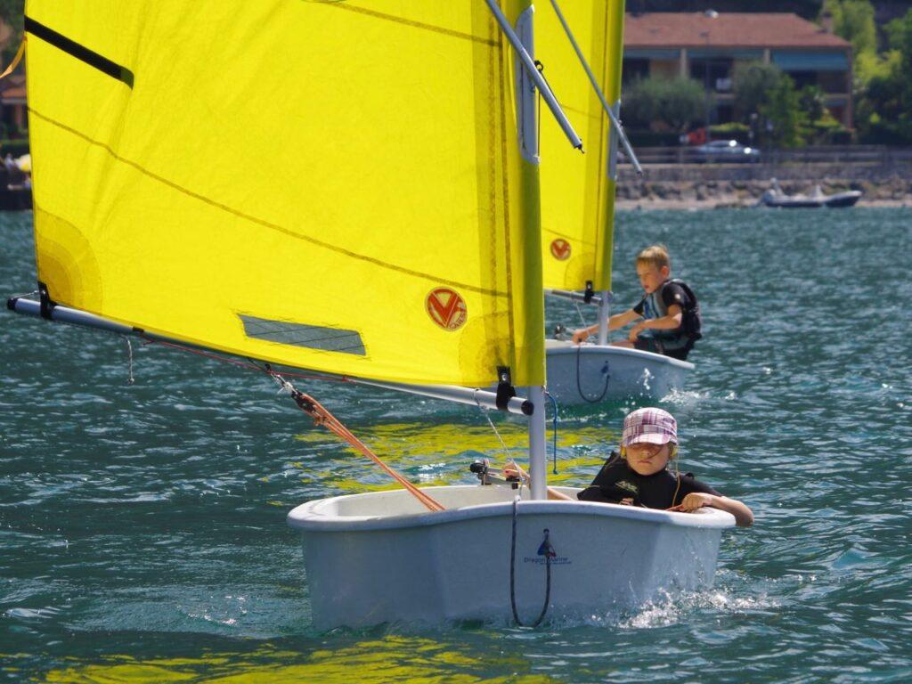 Zwei Kinder segeln in Optimist